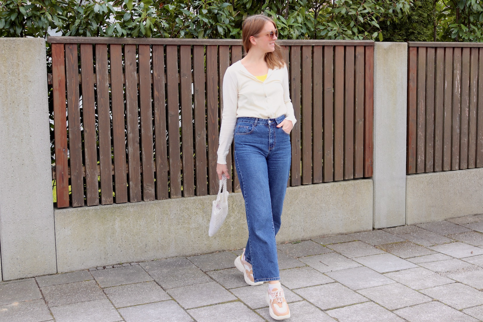 Casual Spring Look. Fashion and Style Blog Girl from Heartfelt Hunt. Girl with blonde hair wearing a cardigan, yellow top, 70s sunglasses, wide leg jeans, pearl bag and chunky sneakers.