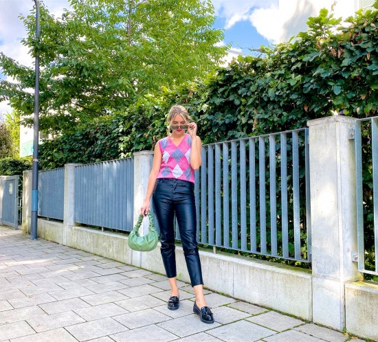 Check Vest. Fashion Blogger Girl by Style Blog Heartfelt Hunt. Girl with blond hair wearing a check vest, faux leather pants, green sunglasses, green ruched bag and loafers.