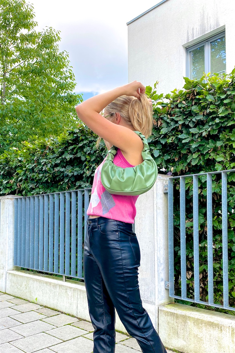 Check Vest. Fashion and Style Blog Girl from Heartfelt Hunt. Girl with blonde hair wearing a check vest, faux leather pants, green sunglasses, green ruched bag and loafers.