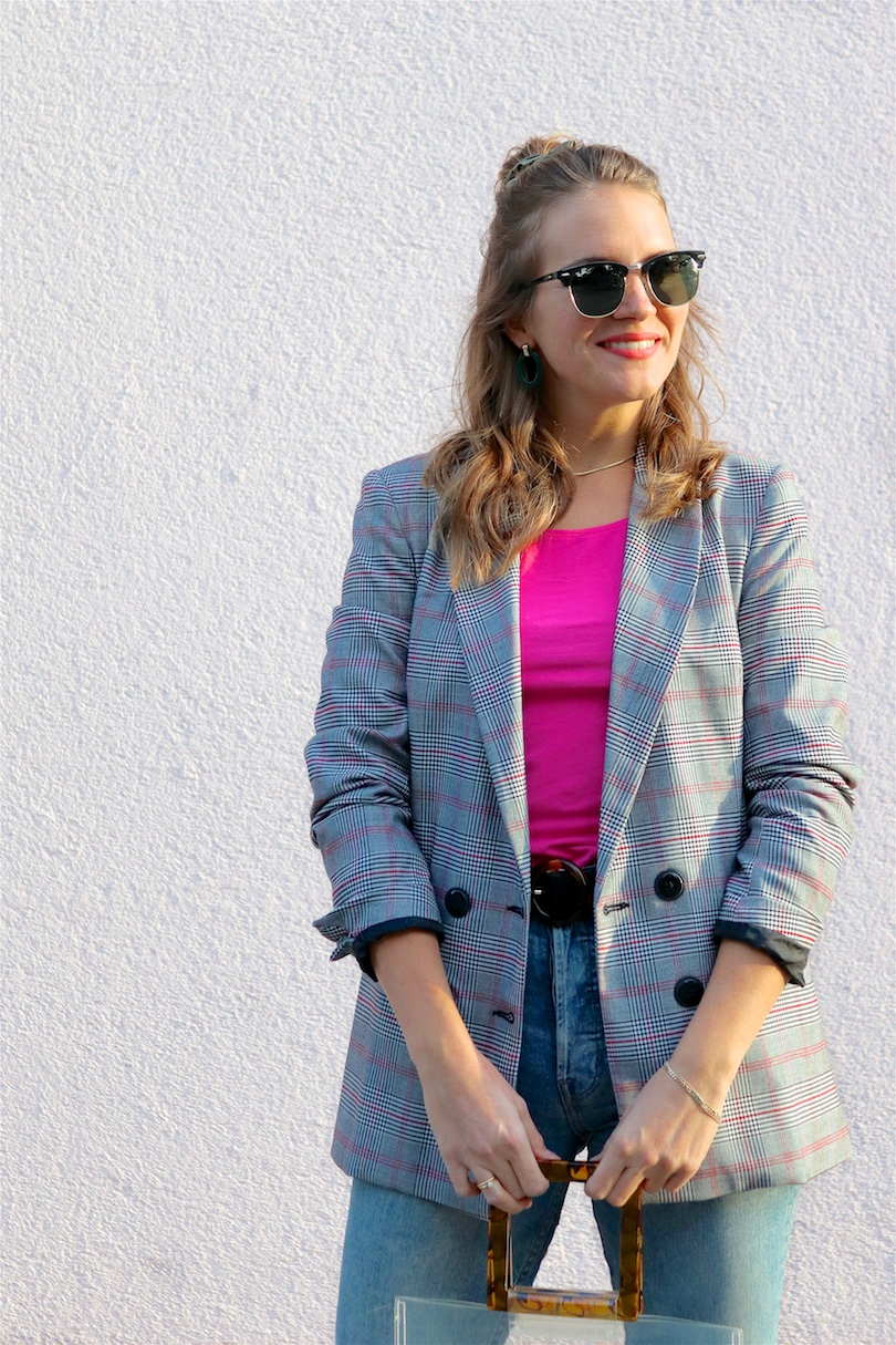 Checked Pink. Fashion Blogger Girl by Style Blog Heartfelt Hunt. Girl with blond hair and scrunchie wearing a checked blazer, pink top, mom jeans, green earrings, green sunglasses, transparent bag, belt and Timberland boots.