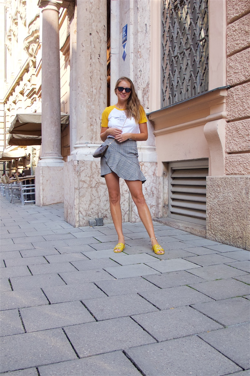 Checked Ruffled Skirt. Fashion and Style Blog Girl from Heartfelt Hunt. Girl with blonde hair wearing a checked ruffled skirt, t-shirt, Louis Vuitton bag, sunglasses and mules with pearls.