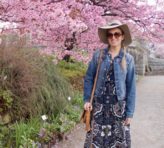 Cherry Blossom. Fashion Blogger Girl by Style Blog Heartfelt Hunt. Girl with blond dutch side braid wearing a flower dress, denim jacket, floppy hat, tassel bag and boots.