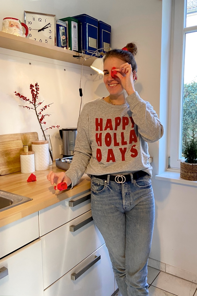 Christmas Cookies. Fashion and Style Blog Girl from Heartfelt Hunt. Girl with blonde, high messy bun and red satin bow wearing a Christmas sweater, mom jeans and belt.