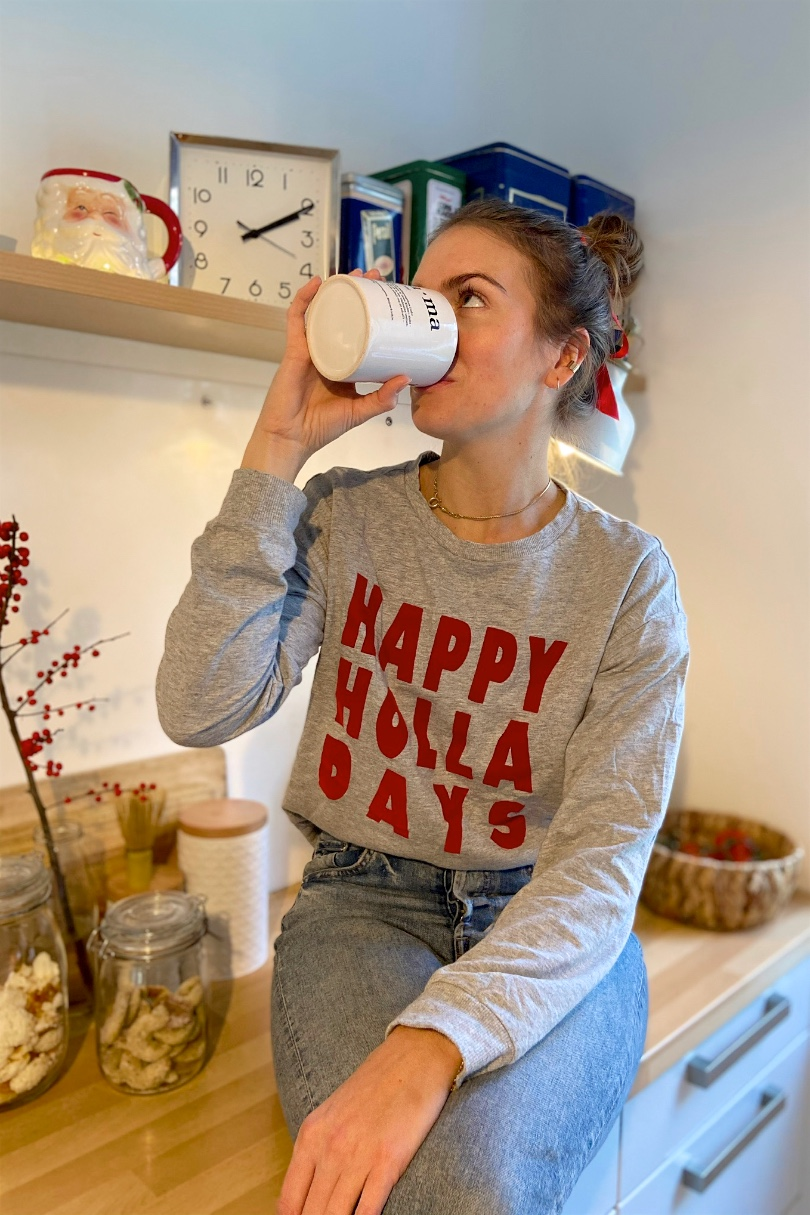 Christmas Cookies. Fashion Blogger Girl by Style Blog Heartfelt Hunt. Girl with blond, high messy bun and red satin bow wearing a Christmas sweater, mom jeans and belt.