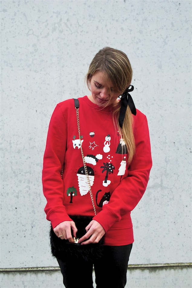 Christmas Sweater. Fashion and Style Blog Girl from Heartfelt Hunt. Girl with blonde ponytail and bow wearing a Christmas sweater, leather pants, faux fur bag and boots.