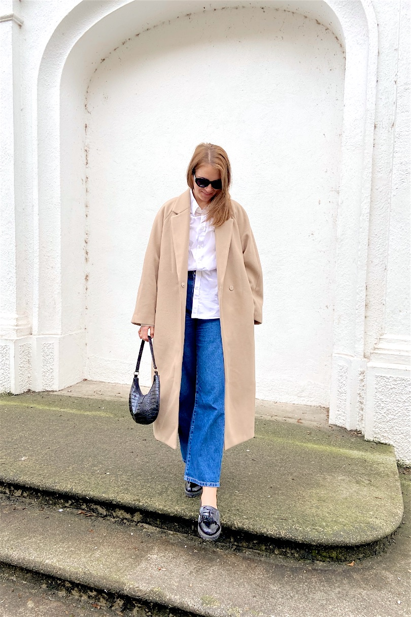 Classic Look. Fashion and Style Blog Girl from Heartfelt Hunt. Girl with blonde hair wearing a camel coat, white shirt, wide leg jeans, slim sunglasses, 90s bag and loafers.