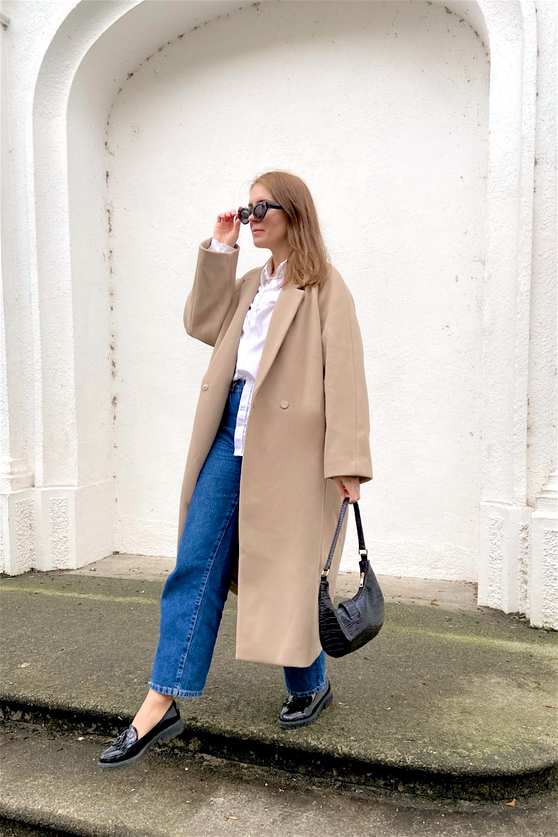 Classic Look. Fashion Blogger Girl by Style Blog Heartfelt Hunt. Girl with blond hair wearing a camel coat, white shirt, wide leg jeans, slim sunglasses, 90s bag and loafers.