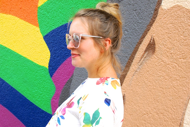 Colorful Love. Fashion and Style Blog Girl from Heartfelt Hunt. Girl with blonde, high messy bun wearing a colorful flower dress, Michael Kors bag and Converse sneakers.