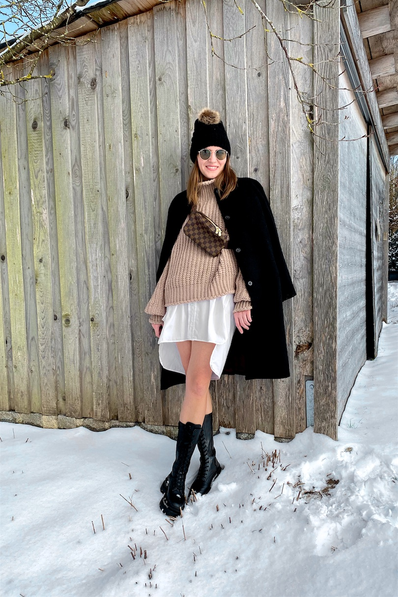 Combat Boots. Fashion and Style Blog Girl from Heartfelt Hunt. Girl with blonde hair wearing a black coat, turtleneck sweater, long blouse, pompom beanie, Louis Vuitton belt bag and combat boots.