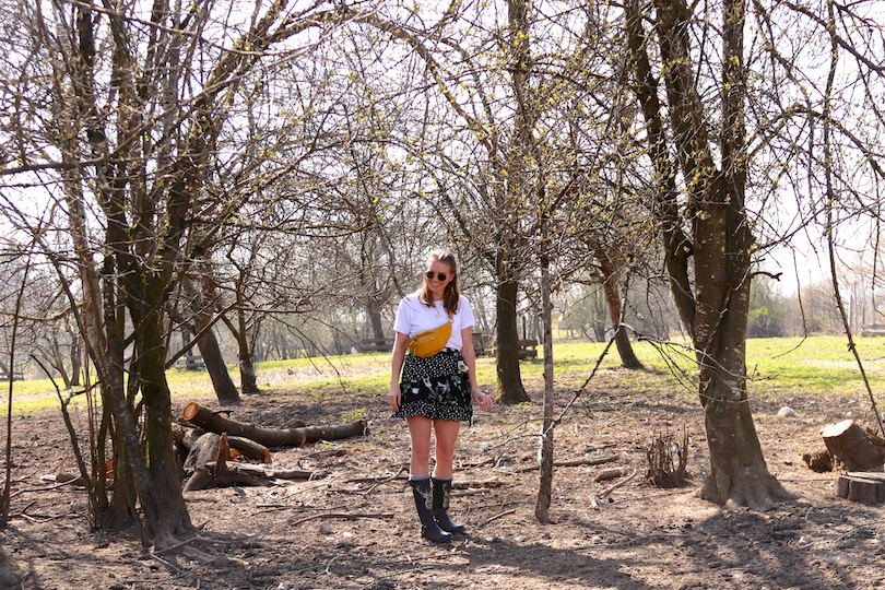 Country Life. Fashion Blogger Girl by Style Blog Heartfelt Hunt. Girl with blond hair wearing a white T-shirt, floral skirt with ruffles, Ray-Ban sunglasses, belt bag and rubber boots.