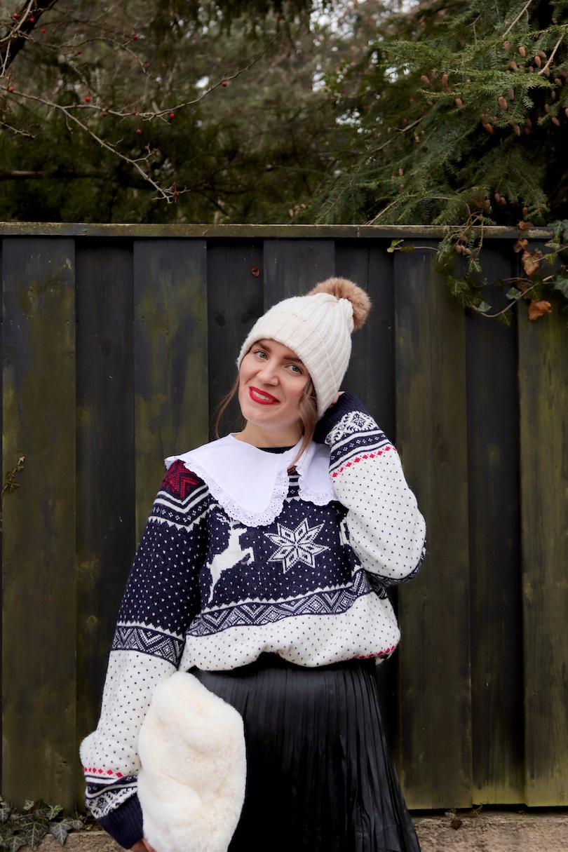 Cozy Chic Holiday Look. Fashion Blogger Girl by Style Blog Heartfelt Hunt. Girl with blond hair and a red bow wearing a pompom beanie, white collar, cozy sweater, pleated skirt, faux fur bag and combat boots.