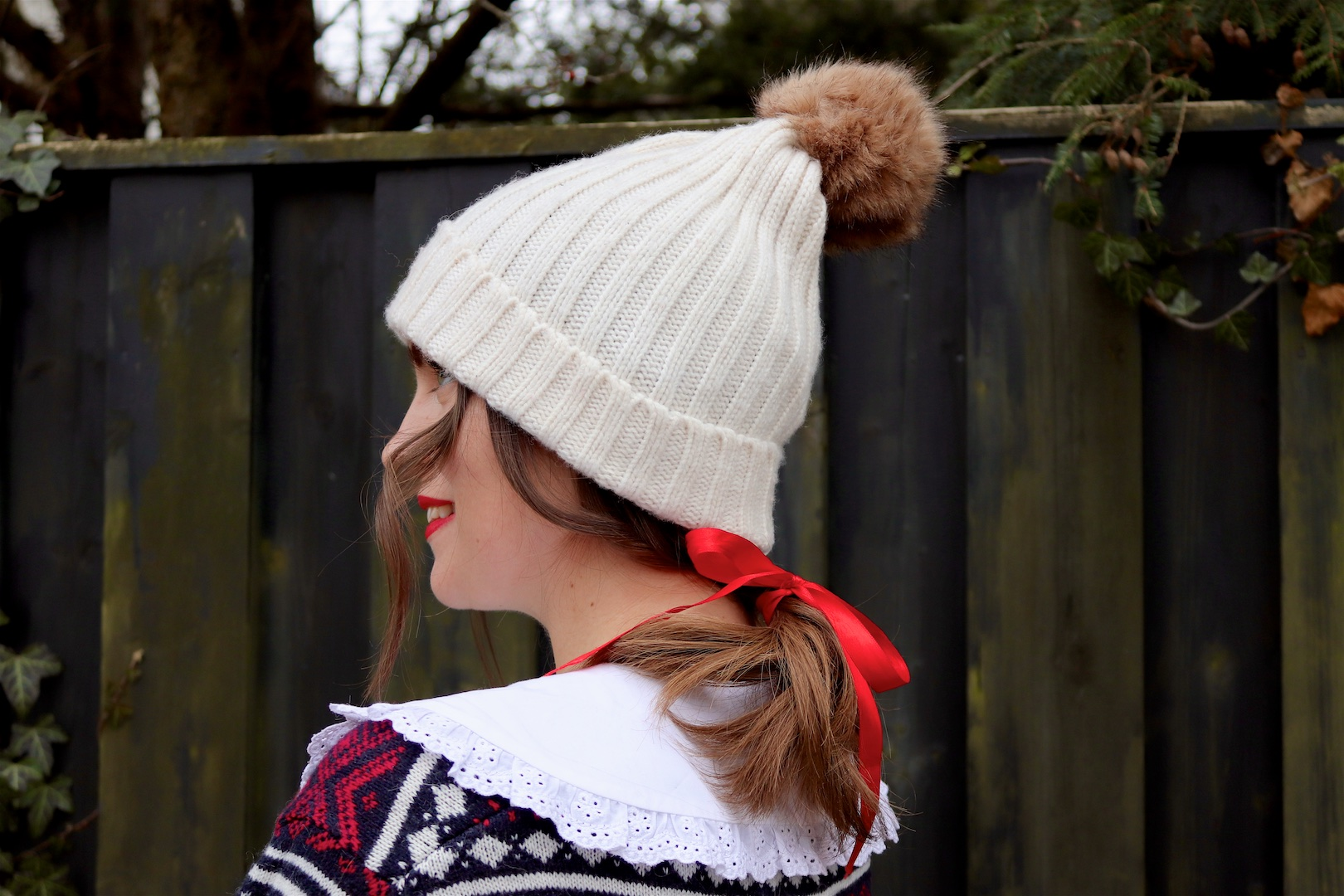Cozy Chic Holiday Look. Fashion and Style Blog Girl from Heartfelt Hunt. Girl with blonde hair and a red bow wearing a pompom beanie, white collar, cozy sweater, pleated skirt, faux fur bag and combat boots.
