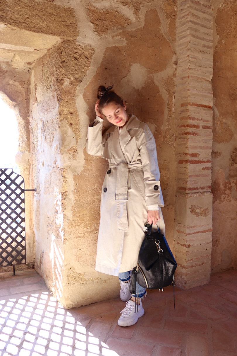 Day Trip Antequera. Fashion and Style Blog Girl from Heartfelt Hunt. Girl with blonde high messy bun and leopard print scrunchie wearing a trench coat, T-shirt, mom jeans, Ray-Ban sunglasses, Rebecca Minkoff backpack and chunky sneakers.