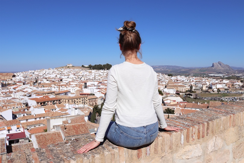 Day Trip Antequera. Fashion Blogger Girl by Style Blog Heartfelt Hunt. Girl with blond high messy bun and leopard print scrunchie wearing a trench coat, T-shirt, mom jeans, Ray-Ban sunglasses, Rebecca Minkoff backpack and chunky sneakers.