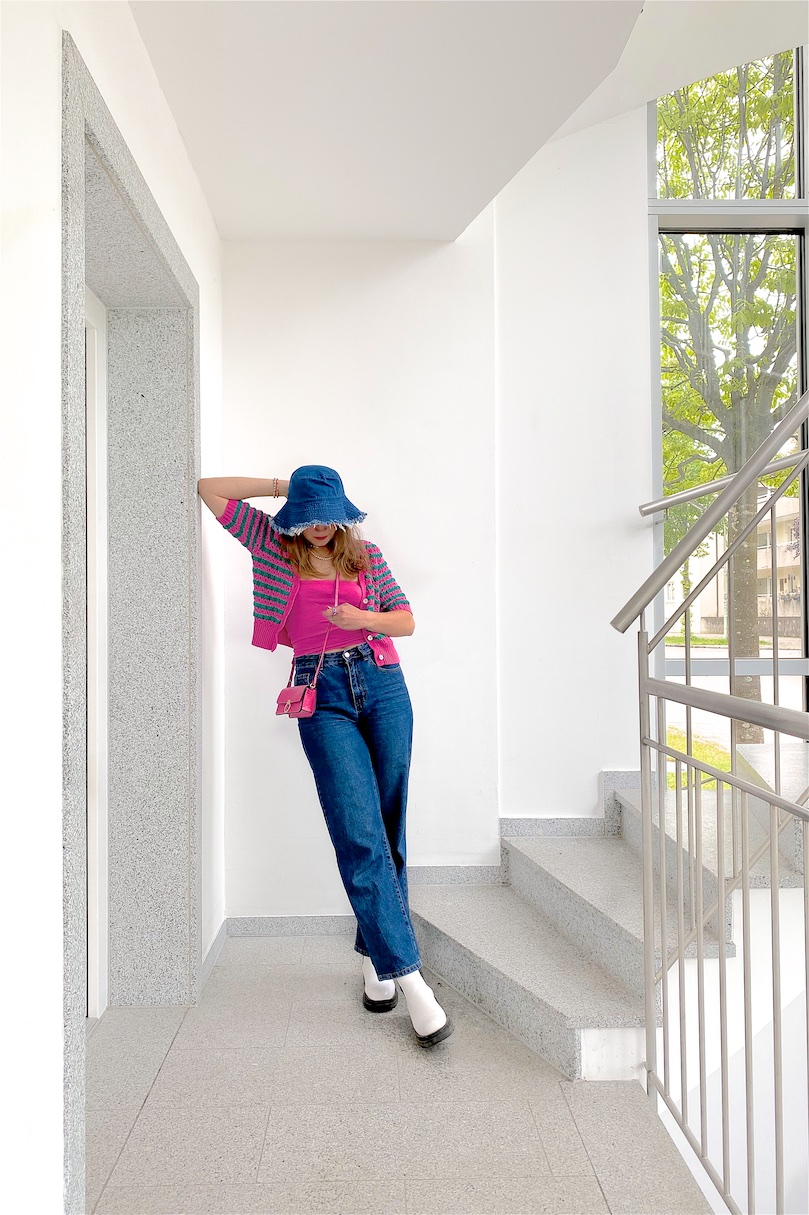 Denim Bucket Hat. Fashion and Style Blog Girl from Heartfelt Hunt. Girl with blonde, loose curls wearing a denim bucket hat, pink cardigan, pink mini bag, wide leg jeans and white chunky boots.