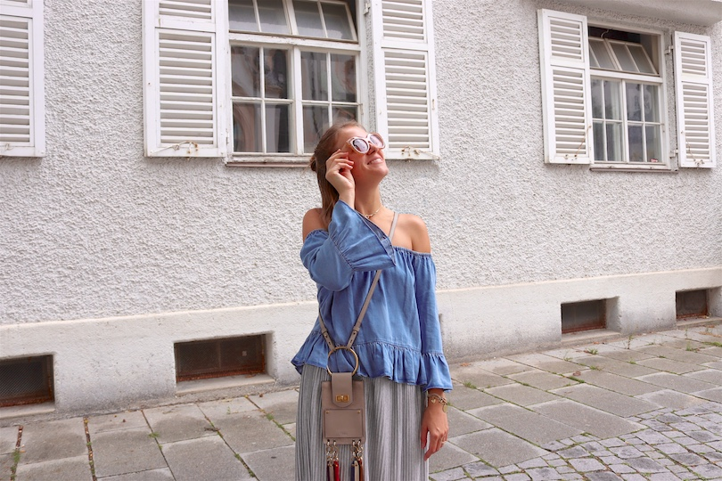 Denim Off Shoulder. Fashion and Style Blog Girl from Heartfelt Hunt. Girl with blonde half-up half-down messy bun wearing a denim off shoulder top, pleated skirt, nude sunglasses, Chloé bag and adidas sneakers.