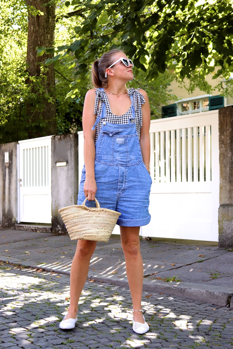 Denim Overall Gingham. Fashion and Style Blog Girl from Heartfelt Hunt. Girl with blonde ponytail wearing a denim overall, gingham swimsuit, heart-shaped sunglasses, straw bag and white flats.