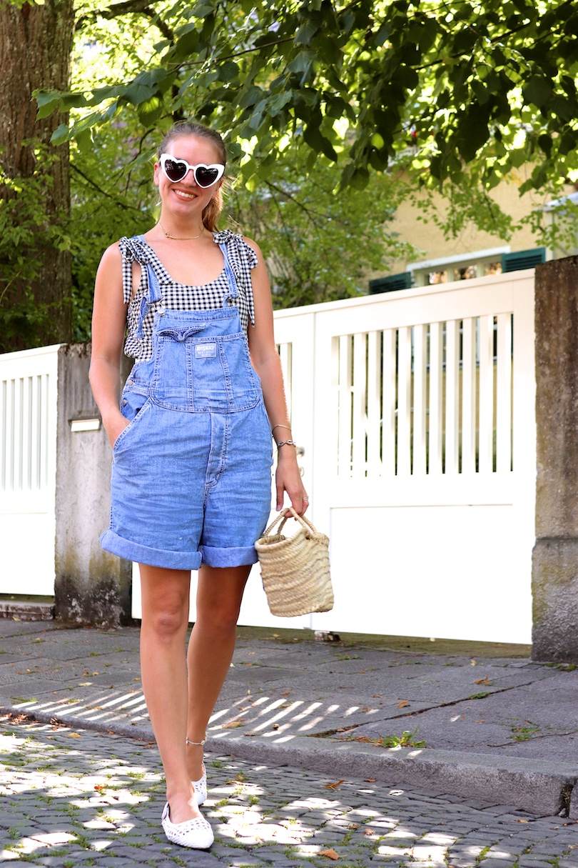 Denim Overall Gingham. Fashion Blogger Girl by Style Blog Heartfelt Hunt. Girl with blond ponytail wearing a denim overall, gingham swimsuit, heart-shaped sunglasses, straw bag and white flats.