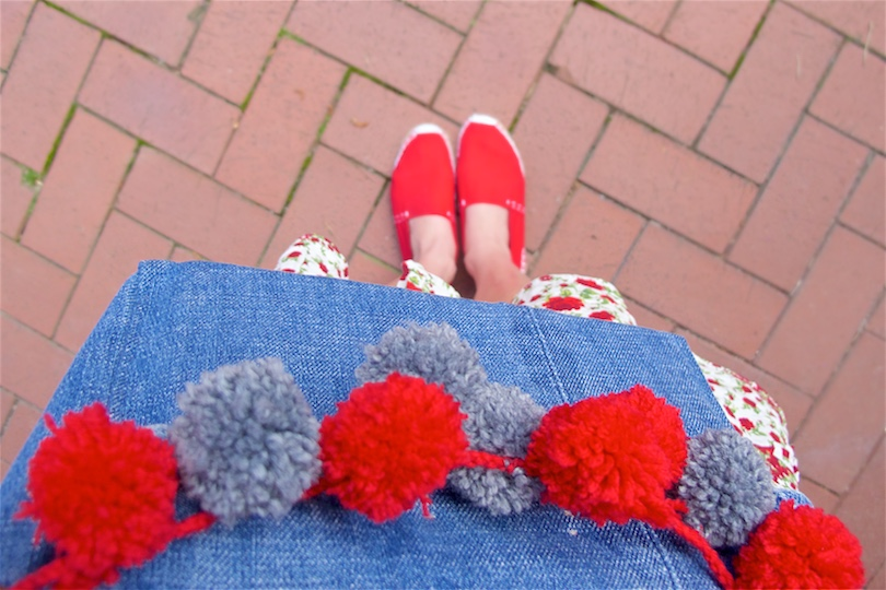 Denim Pompon Bag. Fashion and Style Blog Girl from Heartfelt Hunt. Girl with two blonde pigtail braids wearing a flower dress, red espadrilles and denim pompon bag.