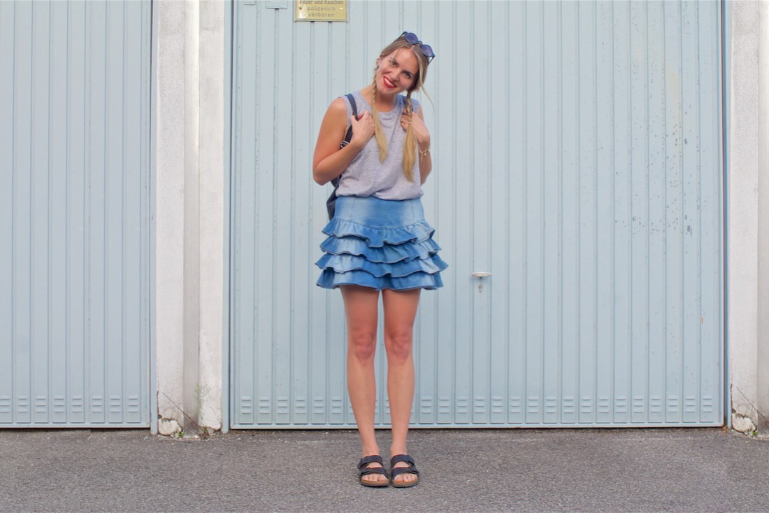 Denim Ruching. Fashion Blogger Girl by Style Blog Heartfelt Hunt. Girl with two blond pigtail braids wearing a denim ruching skirt, oversized top, backpack, sunglasses and Birkenstock sandals.