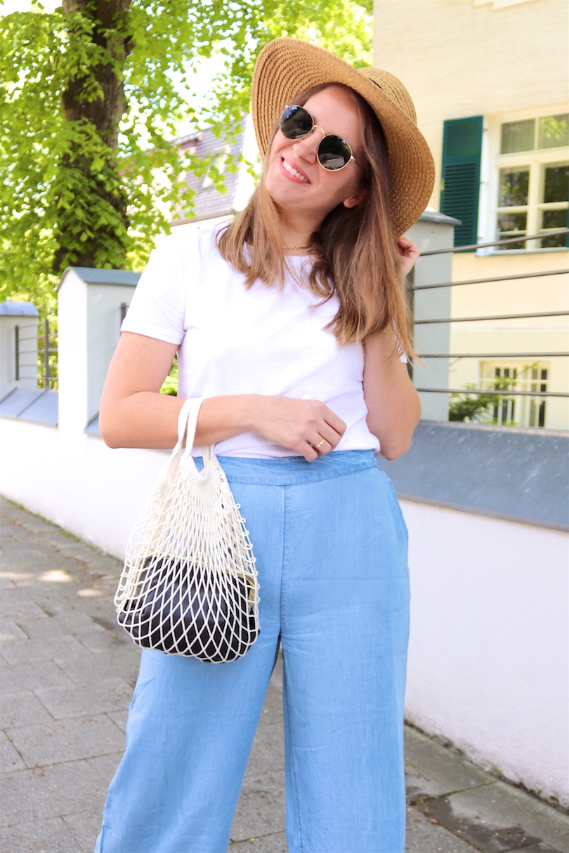 Denim Ruffles. Fashion and Style Blog Girl from Heartfelt Hunt. Girl with blonde hair wearing pants with denim ruffles, T-shirt, straw hat, Ray-Ban sunglasses, net bag and straw flats.