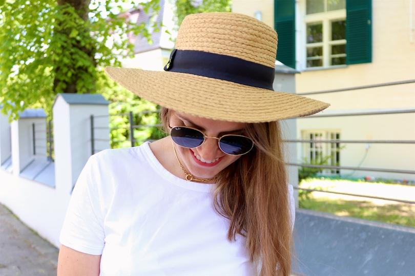 Denim Ruffles. Fashion Blogger Girl by Style Blog Heartfelt Hunt. Girl with blond hair wearing pants with denim ruffles, T-shirt, straw hat, Ray-Ban sunglasses, net bag and straw flats.