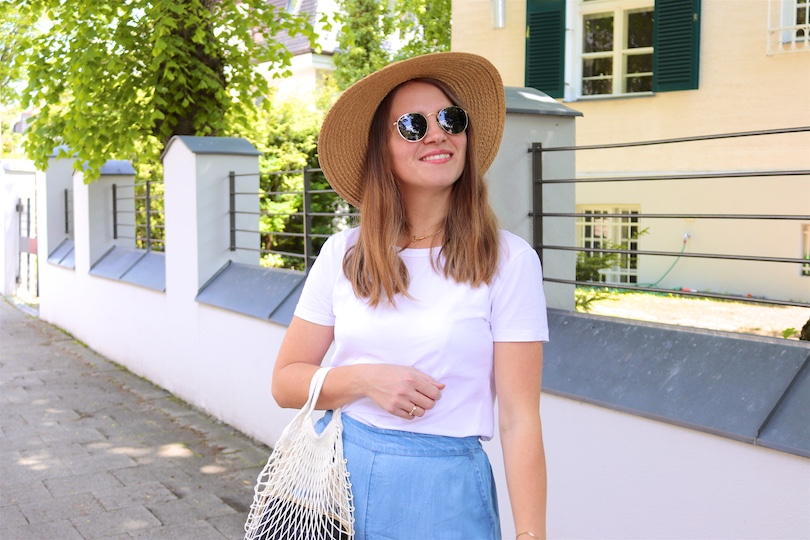 Denim Ruffles. Fashion Blogger Girl by Style Blog Heartfelt Hunt. Girl with blond hair wearing pants with denim ruffles, T-shirt, straw hat, Ray-Ban sunglasses, net bag and straw flats.