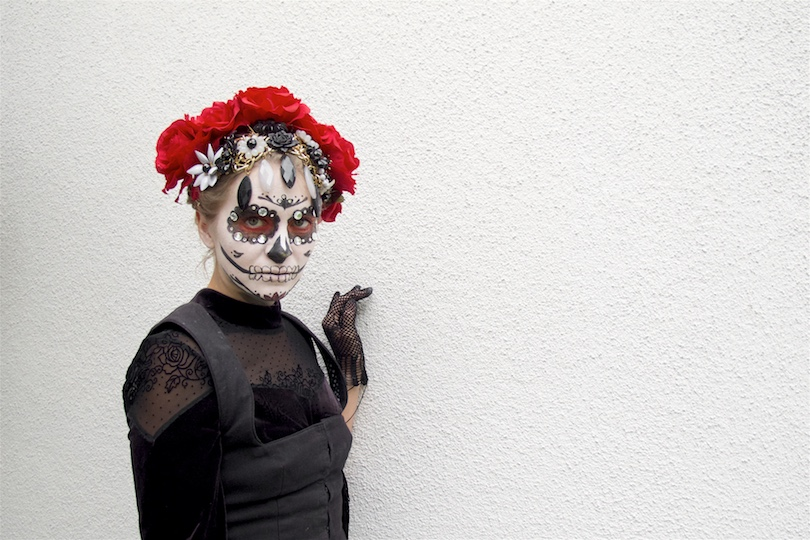Dia De Los Muertos 2018. Fashion Blogger Girl by Style Blog Heartfelt Hunt. Girl with blond hair and flower crown showing her Halloween costume wearing a dress with fringes, embroidered skirt, bodice and flower necklace.