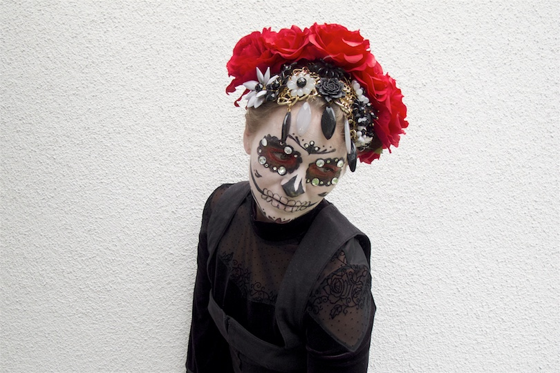 Dia De Los Muertos 2018. Fashion and Style Blog Girl from Heartfelt Hunt. Girl with blonde hair and flower crown showing her Halloween costume wearing a dress with fringes, embroidered skirt, bodice and flower necklace.
