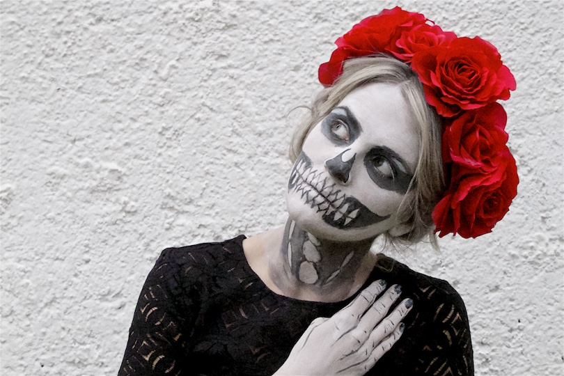 Día De Los Muertos. Fashion Blogger Girl by Style Blog Heartfelt Hunt. Girl with blond halo braid wearing a black cocktail dress, tulle dress, petticoat, lace top with trumpet sleeves, boots and flower crown for a Day of the Dead or Halloween look.