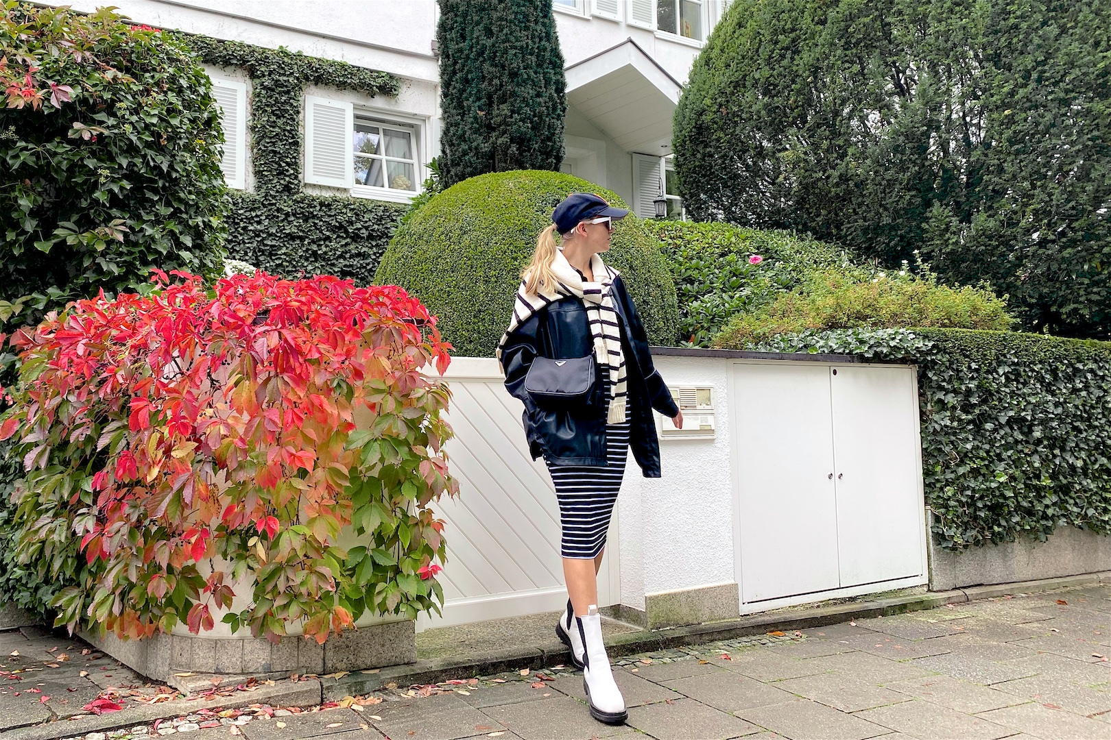 Double Stripes. Fashion Blogger Girl by Style Blog Heartfelt Hunt. Girl with blond ponytail wearing a cap, faux leather shacket, striped sweater, striped dress, 90s bag and white, chunky boots.