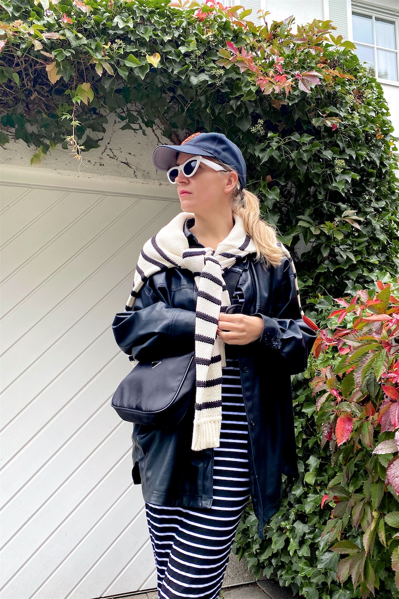 Double Stripes. Fashion and Style Blog Girl from Heartfelt Hunt. Girl with blonde ponytail wearing a cap, faux leather shacket, striped sweater, striped dress, 90s bag and white, chunky boots.