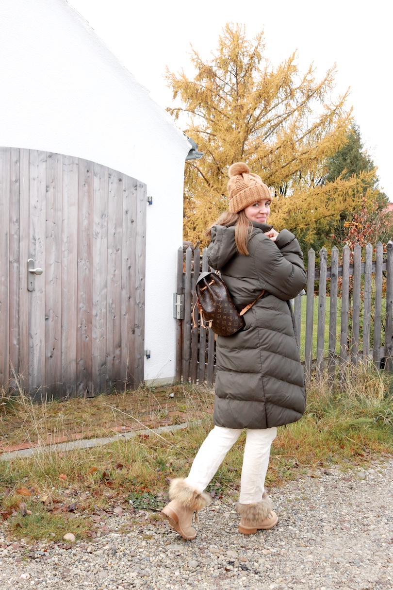 Down Coat. Fashion Blogger Girl by Style Blog Heartfelt Hunt. Girl with blond hair wearing a down coat, pompom beanie, scarf, chunky sweater, corduroy pants, Louis Vuitton backpack and faux fur boots.