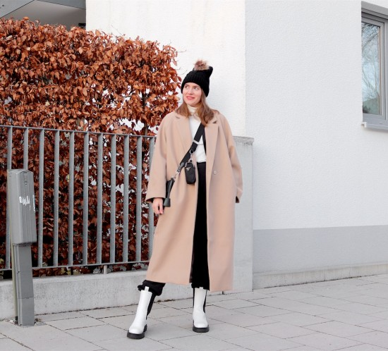 Elevated Sweatpants Look. Fashion Blogger Girl by Style Blog Heartfelt Hunt. Girl with blond hair wearing a camel coat, pompom beanie, turtleneck sweater, sweatpants, 90s bag and white boots.