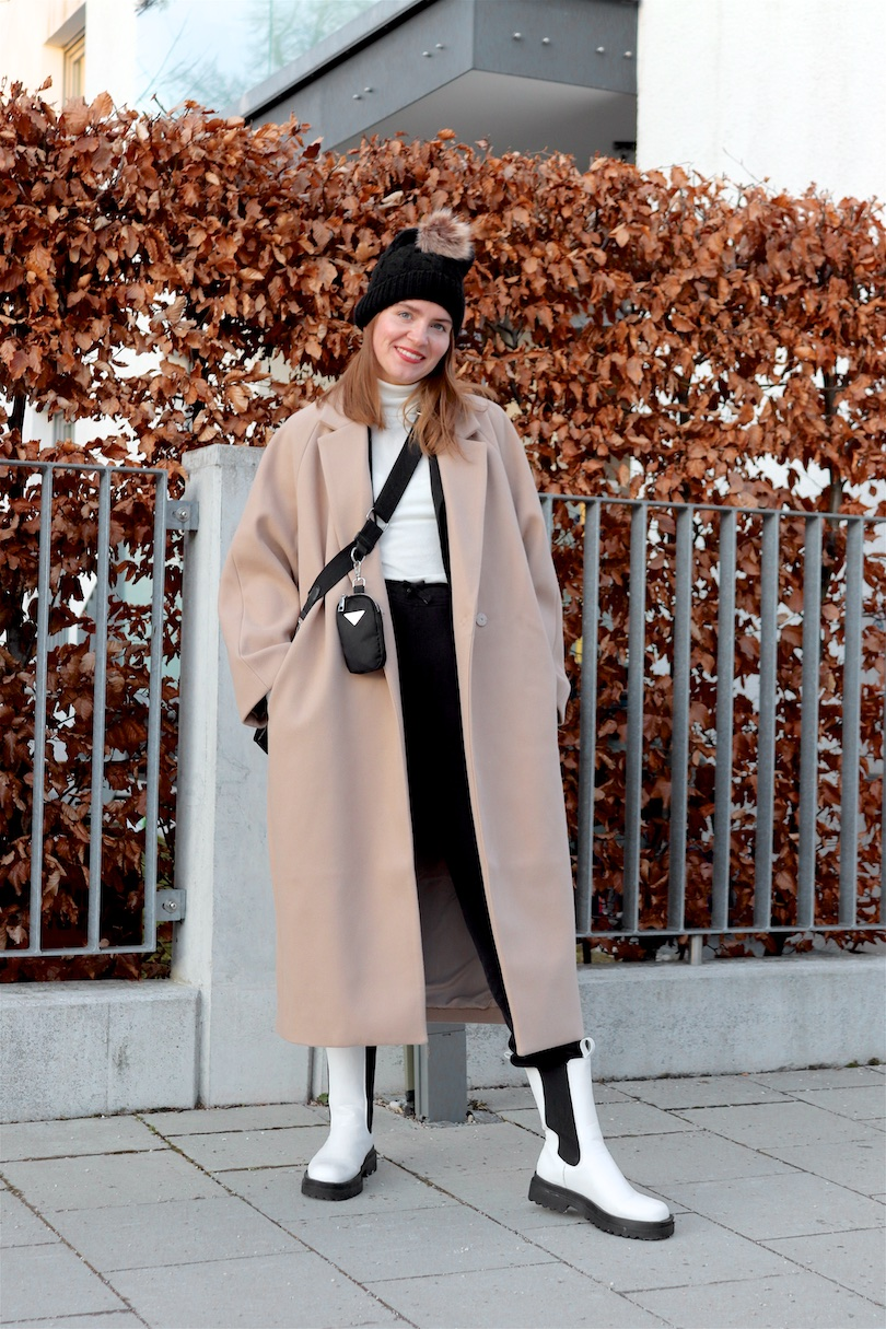 Elevated Sweatpants Look. Fashion and Style Blog Girl from Heartfelt Hunt. Girl with blonde hair wearing a camel coat, pompom beanie, turtleneck sweater, sweatpants, 90s bag and white boots.