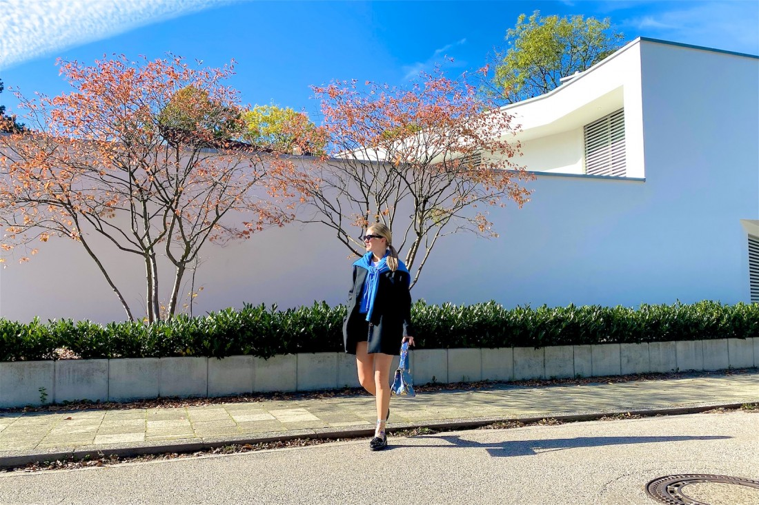 Fall Blues. Fashion Blogger Girl by Style Blog Heartfelt Hunt. Girl with blond sleek ponytail wearing a blue sweater, oversized blazer, slim sunglasses, faux leather shorts, blue Louis Vuitton bag, floral socks and chunky loafers.