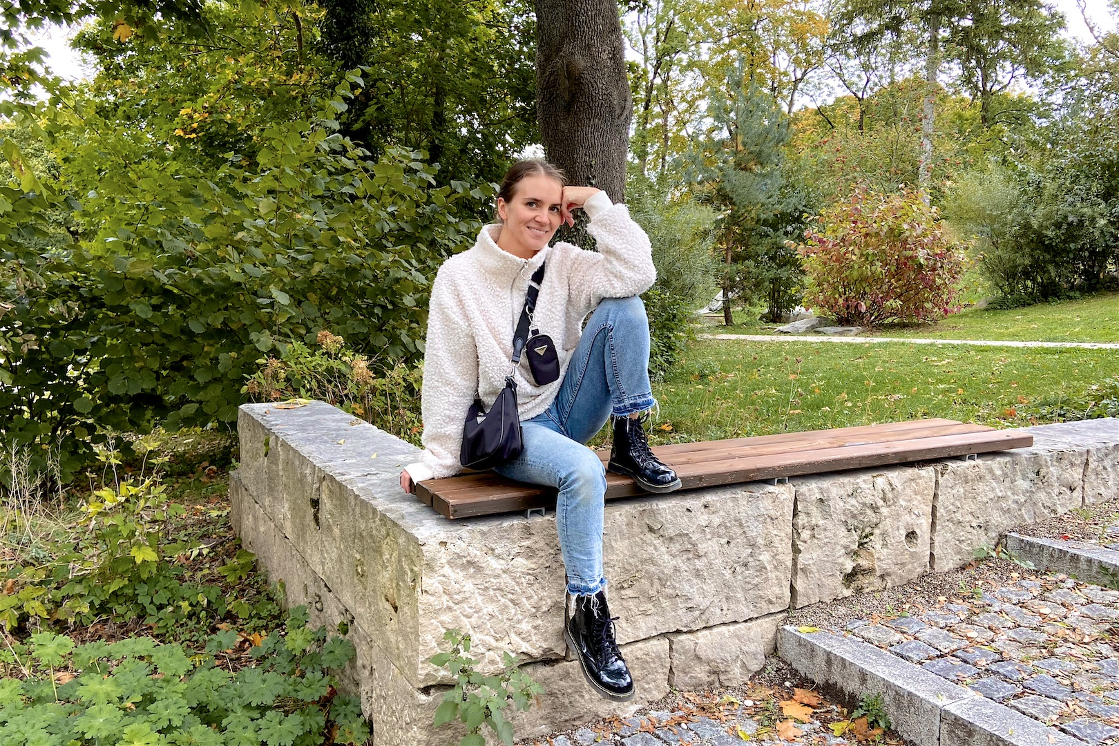 Fall Essentials 2020. Fashion Blogger Girl by Style Blog Heartfelt Hunt. Girl with blond, low bun wearing a teddy sweater, mom jeans, black bag and glossy boots showing her fall essentials for 2020.