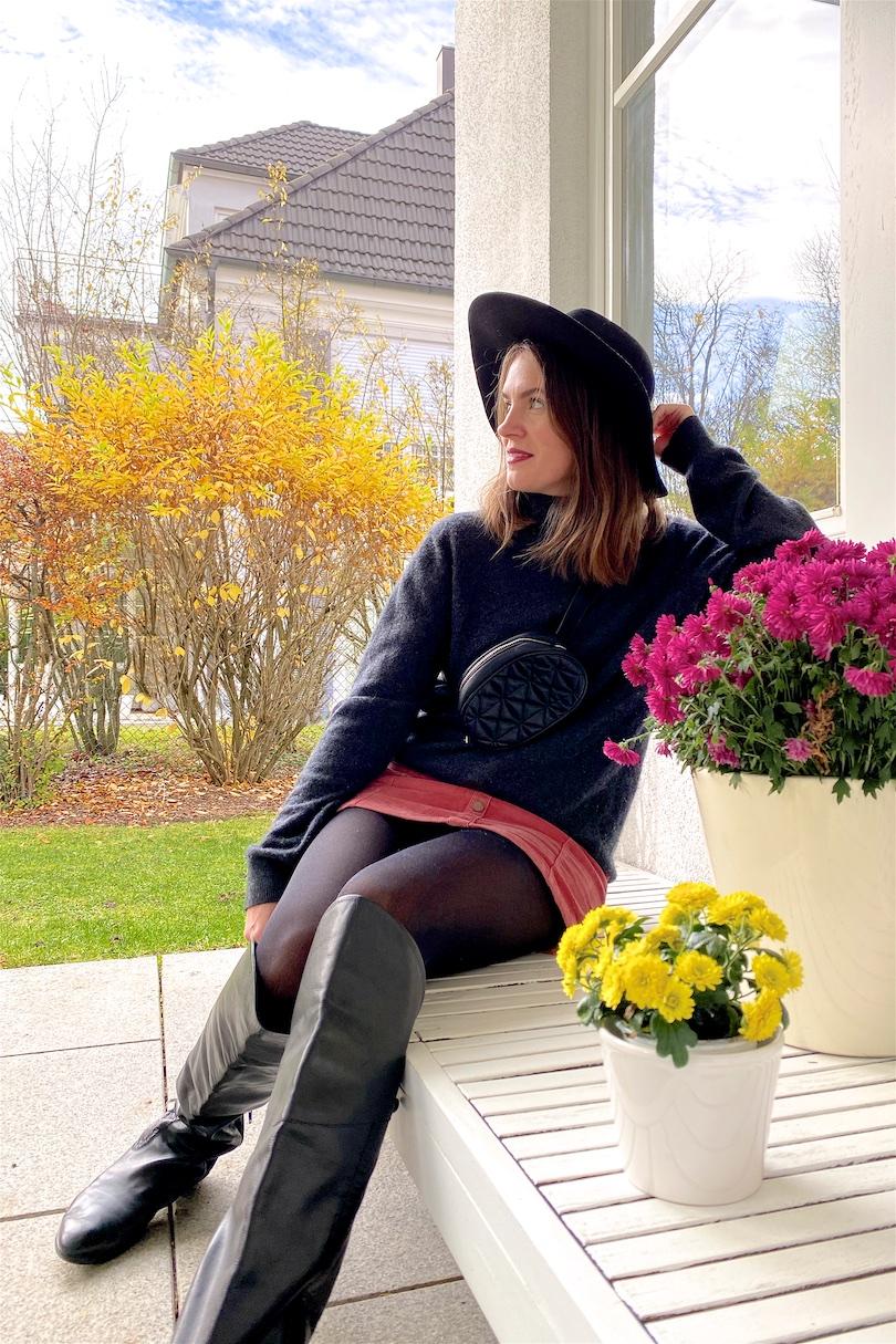 Fall Light. Fashion Blogger Girl by Style Blog Heartfelt Hunt. Girl with blond hair wearing a black hat, turtleneck sweater, velvet skirt, belt bag and over knee boots.