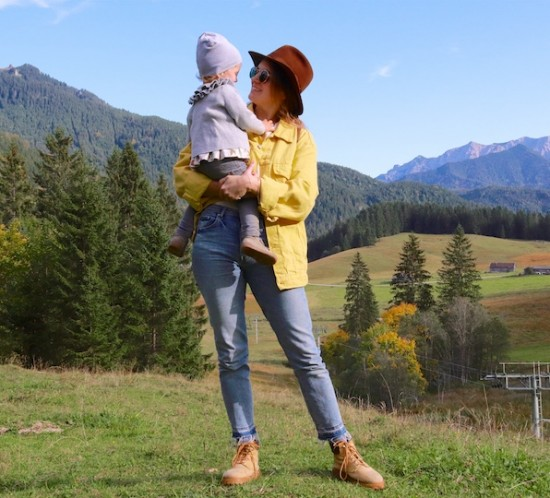 Fall Trip. Fashion Blogger Girl by Style Blog Heartfelt Hunt. Girl with blond, low messy bun wearing a yellow denim jacket, flower T-shirt, brown hat, Ray-Ban sunglasses, Michael Kors backpack, mom jeans and boots.