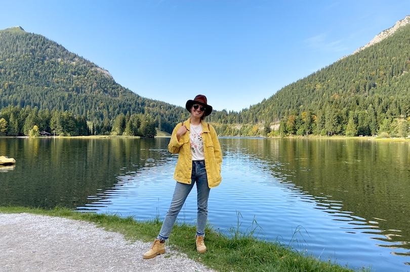 Fall Trip. Fashion and Style Blog Girl from Heartfelt Hunt. Girl with blonde, low messy bun wearing a yellow denim jacket, flower T-shirt, brown hat, Ray-Ban sunglasses, Michael Kors backpack, mom jeans and boots.