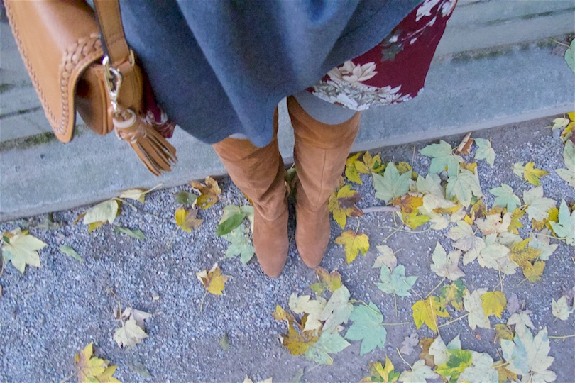 Fall Vibes. Fashion and Style Blog Girl from Heartfelt Hunt. Girl with blonde, loose curls wearing a floral dress, poncho, tassel bag and suede thigh high boots.