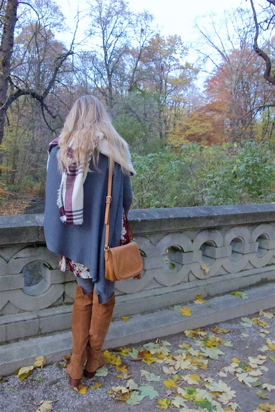 Fall Vibes. Fashion Blogger Girl by Style Blog Heartfelt Hunt. Girl with blond, loose curls wearing a floral dress, poncho, plaid scarf, tassel bag and suede thigh high boots.