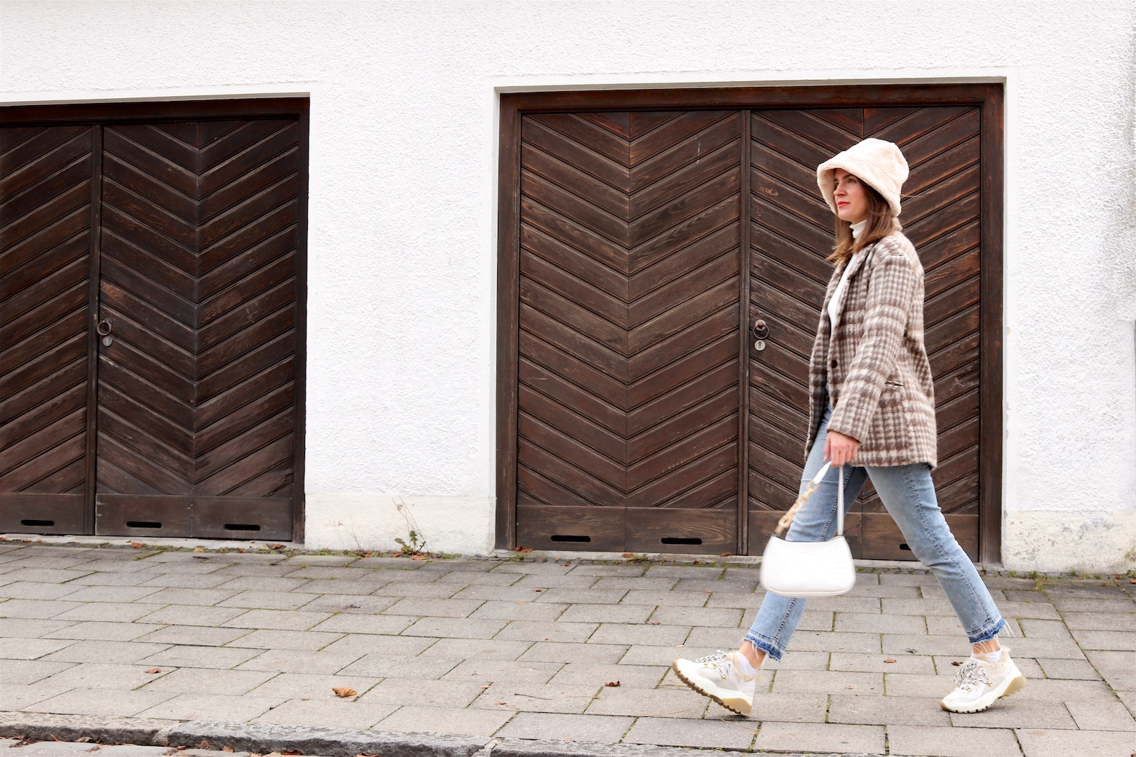 Faux Fur Bucket Hat. Fashion Blogger Girl by Style Blog Heartfelt Hunt. Girl with blond hair wearing a faux fur bucket hat, plaid blazer, white turtleneck, mom jeans, white bag and faux fur sneakers.
