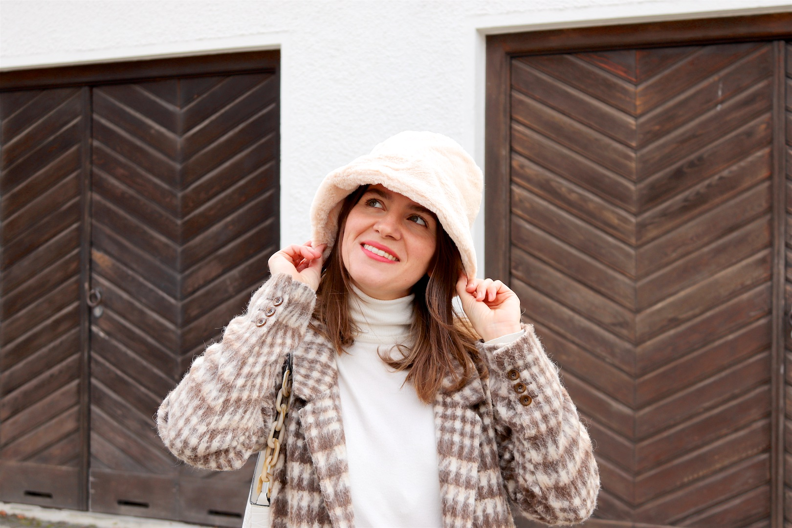 Faux Fur Bucket Hat. Fashion and Style Blog Girl from Heartfelt Hunt. Girl with blonde hair wearing a faux fur bucket hat, plaid blazer, white turtleneck, mom jeans, white bag and faux fur sneakers.