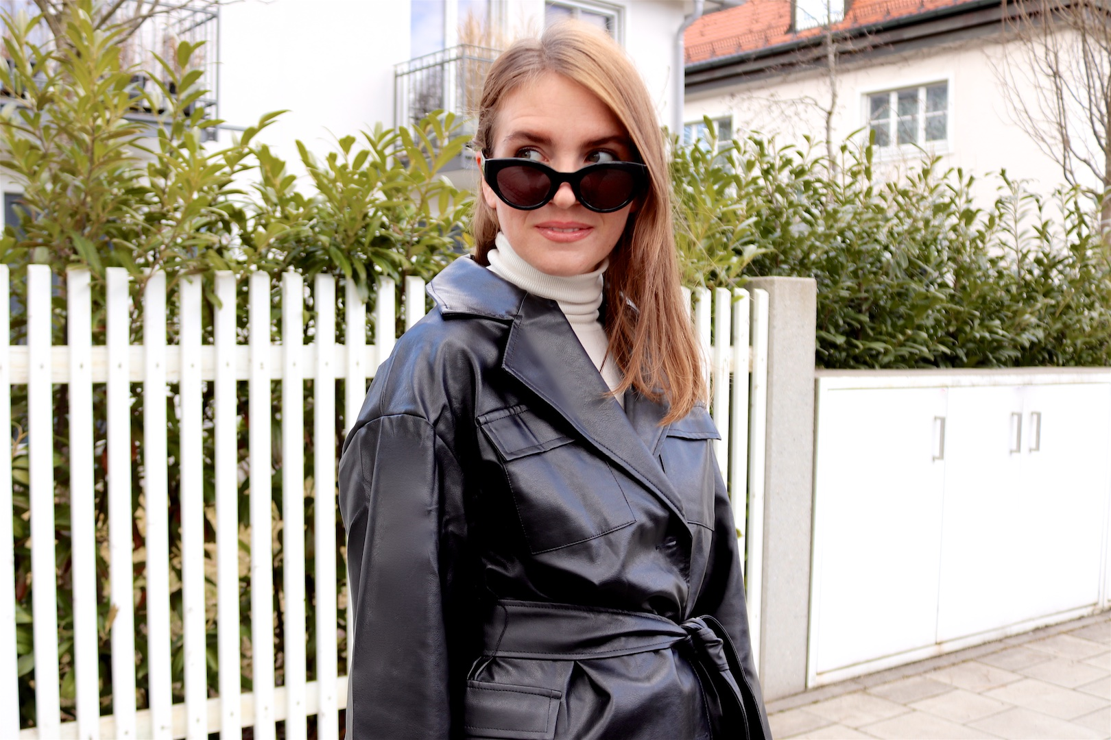 Faux Leather Blazer. Fashion Blogger Girl by Style Blog Heartfelt Hunt. Girl with blond hair showing a faux leather blazer, white turtleneck, mom jeans, slim sunglasses, 90s bag and chunky chelsea boots.