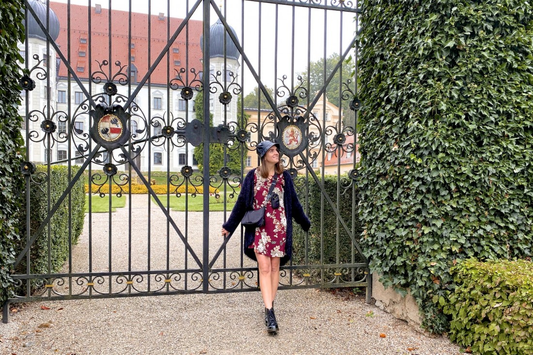 Faux Leather Bucket Hat. Fashion Blogger Girl by Style Blog Heartfelt Hunt. Girl with blond hair wearing a faux leather bucket hat, cozy cardigan, burgundy flower dress, sporty bag and glossy boots.