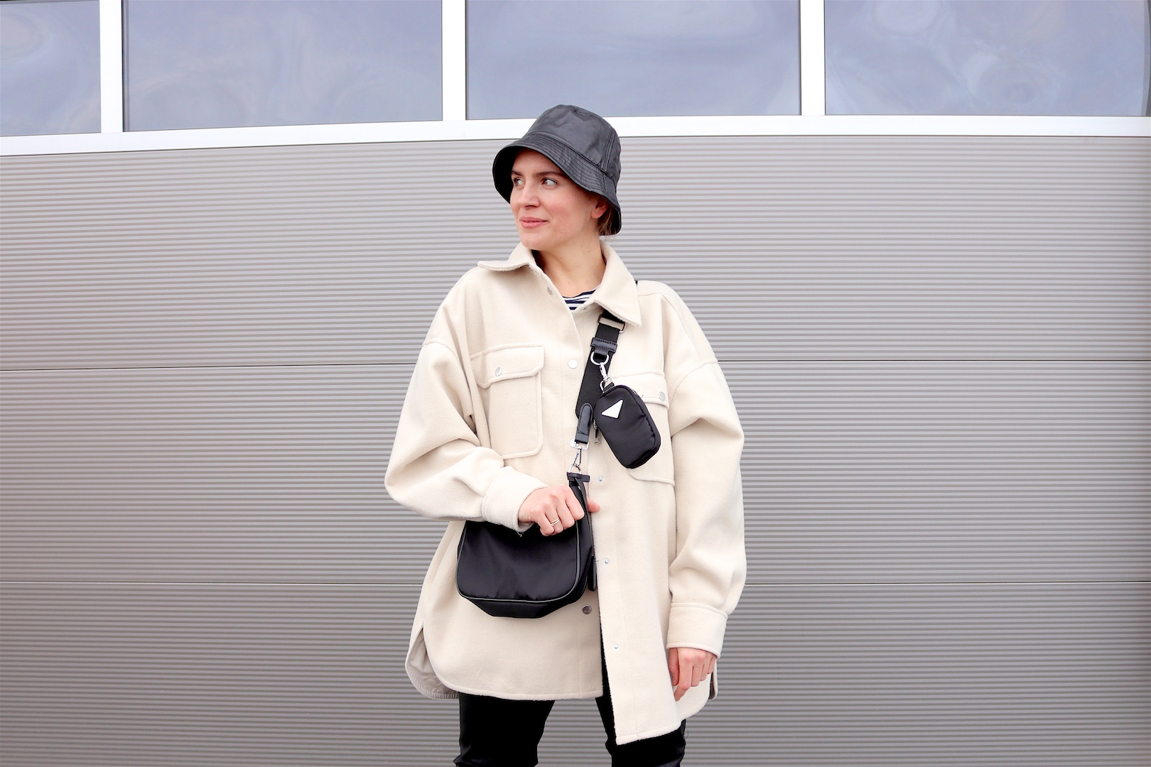 Faux Leather Look. Fashion Blogger Girl by Style Blog Heartfelt Hunt. Girl with blond braid wearing a faux leather bucket hat, shacket, striped tee, faux leather pants, 90s bag and faux leather combat boots.