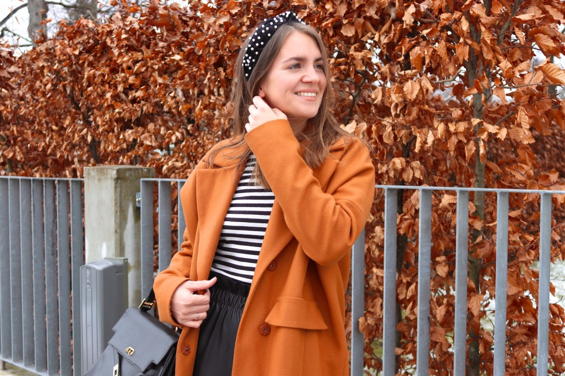 Faux Leather Pants. Fashion Blogger Girl by Style Blog Heartfelt Hunt. Girl with blond hair and pearl headband wearing faux leather pants, striped turtleneck sweater, coat, vintage MCM bag and sock boots.