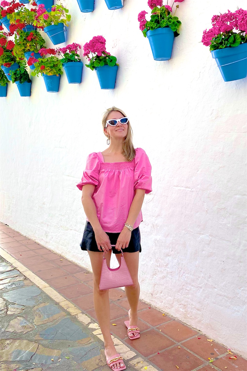 Faux Leather Shorts. Fashion Blogger Girl by Style Blog Heartfelt Hunt. Girl with blond hair wearing faux leather shorts, puff sleeve blouse, white sunglasses, pink Staud bag and pink sandals.