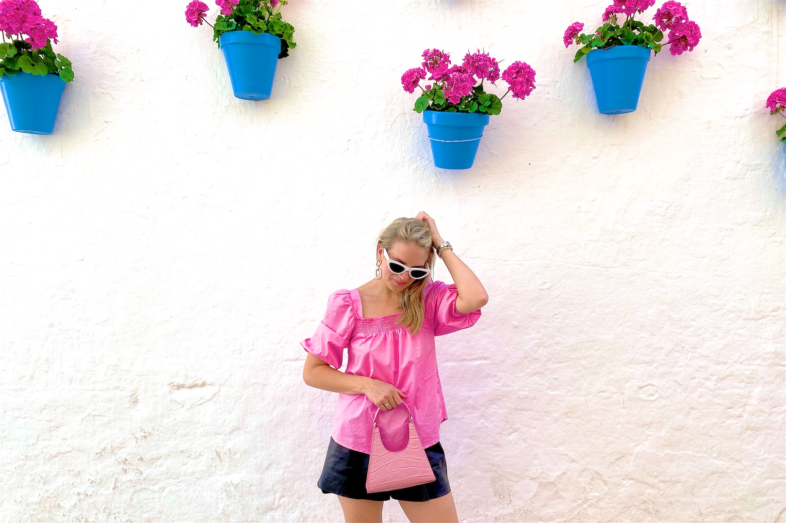 Faux Leather Shorts. Fashion and Style Blog Girl from Heartfelt Hunt. Girl with blonde hair wearing faux leather shorts, puff sleeve blouse, white sunglasses, pink Staud bag and pink sandals.